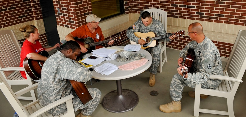 """Soldiers with the Warrior Transition Unit practice guitar during their lesson as part of the """"Music for Morale"""" program at Fort Eustis, Va., July 11, 2013. The program is available to all WTU Soldiers, regardless of guitar-playing experience. (U.S. Air Force photo by Staff Sgt. Wesley Farnsworth/Released)"""