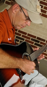 """Woody Groton, Fort Eustis Warrior Transition Unit site coordinator for the military adaptive sport program, plays his guitar during the """"Music for Morale"""" program at Fort Eustis, Va., July 11, 2013. Groton started the program as a way to share his love for playing guitar while helping Soldiers in their recovery process. (U.S. Air Force photo by Staff Sgt. Wesley Farnsworth/Released)"""