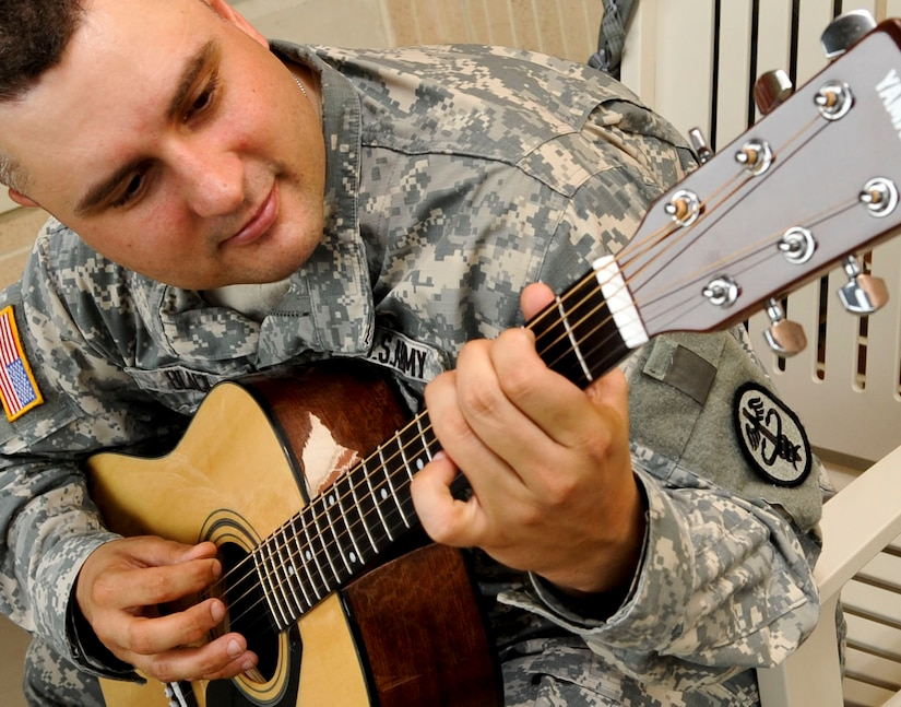 """U.S. Army Sgt. Scott Black, a Warrior Transition Unit  healing warrior, plays his guitar at the WTU  at Fort Eustis, Va., July 11, 2013. Black is one of 30 Soldiers who have participated in the free """"Music for Morale"""" program offered as part of the WTU's healing program. (U.S. Air Force photo by Staff Sgt. Wesley Farnsworth/Released)"""