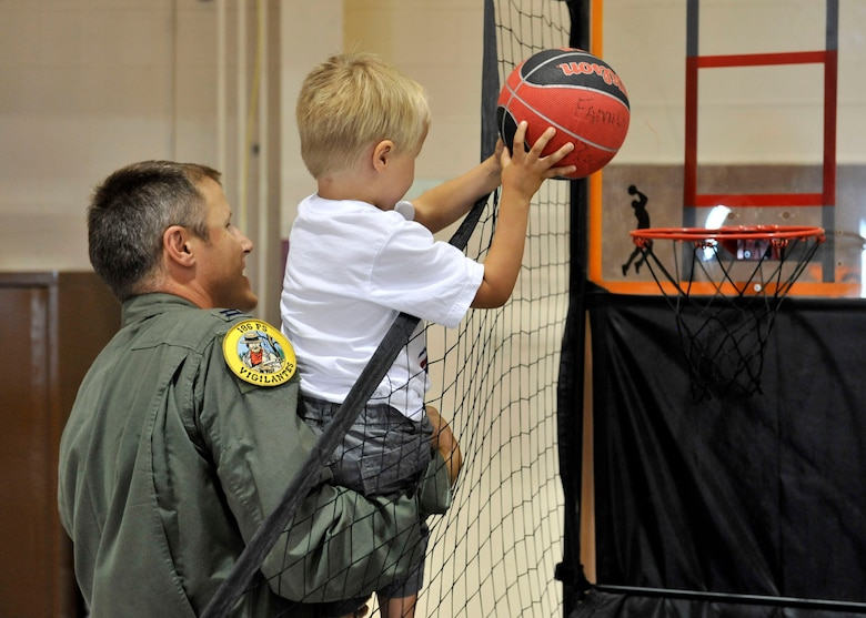 Capt. Clay Bird helps a young basketball player sink a basket during the Montana Air National Guard Family Day on Aug. 11, 2012. (U.S. Air Force photo/Staff Sgt. John Turner)