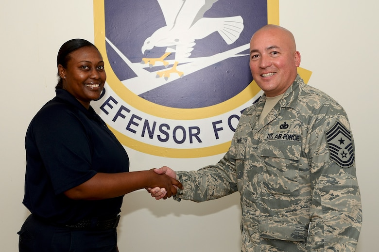 U.S. Air Force Command Chief Master Sgt. Mitchell Brush, Senior Enlisted Advisor to the Chief of the National Guard, National Guard Bureau, Washington D.C., presents Ms. Veronica Dennis, 169th Security Forces Squadron, with a coin for her outstanding work in the unit during his visit with the 169th Fighter Wing, South Carolina Air National Guard at McEntire Joint National Guard Base, S.C., June 17, 2013.  (U.S. Air National Guard photo by Tech. Sgt. Caycee Watson/Released)
