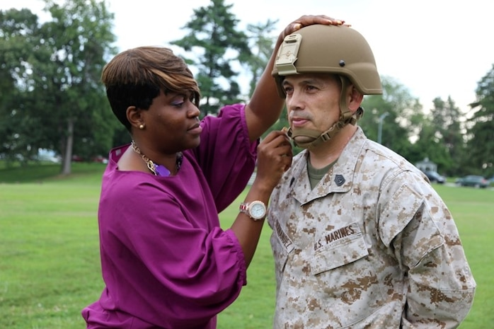 Deidre Hooks, enhanced combat helmet team lead at Marine Corps Systems Command, fits the ECH onto Gunnery Sgt. Jose Hernandez of the MCSC Operations Cell. The helmet passed many stringent test protocols and will be fielded to deploying Marines in the first quarter of fiscal 2014.