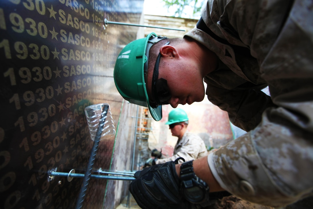 """Lance Cpl. Bennett Russ (right) and Lance Cpl. Taylor Tingey add """"all-threads"""" to foundation wall forms while building a handicap-accessible ramp at Erdmiin Oyun School, July 27. U.S. Marines with 9th Engineer Support Battalion and U.S. Army soldiers with 96th Troop Command are working alongside soldiers with the Mongolian Armed Forces in Nalaikh district, Ulaanbaatar, Mongolia during Exercise Khaan Quest 2013. Khaan Quest is a regularly scheduled, multinational exercise co-sponsored this year by U.S. Marine Corps Forces Pacific, and hosted annually by the MAF. The intent of the ongoing engineering civic action program (ENCAP) project in Nalaikh is to provide valuable training for Mongolian and U.S. armed forces by boosting their interoperability, as well as demonstrate a mutual commitment to local community."""