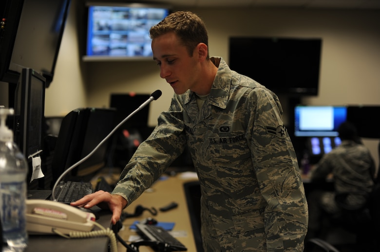 U.S. Air Force Airman 1st Class Timothy Kimball, a junior emergency actions controller with 1st Special Operations Wing Command Post, makes an announcement on the giant voice microphone during an announcement at the 1st SOW Command Post at Hurlburt Field, Fla., July 25, 2013. Kimball, like other 1 SOW/CP personnel, uses the giant voice system to notify the installation populace of flag conditions, weather advisories and potential crisis warnings. (U.S. Air Force Photo / Senior Airman Joe McFadden)