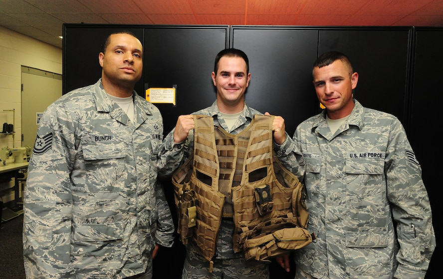 Technical Sgt. Damian Bunch, Senior Airman Ethan Mason, and Staff Sgt. Josh Riffe, aircrew flight equipment members from the 509th Operations Support Squadron pose with a fully constructed Airsave vest at Whiteman Air Force Base, Mo., July 12, 2013. Along with Airman 1st Class Matthew Ford, 509th OSS aircrew flight equipment journeyman, these Airmen were the first individuals on base to be trained on the Air Force's new Airsave vest system. (U.S. Air Force photo by Staff Sgt. Nick Wilson/Released)