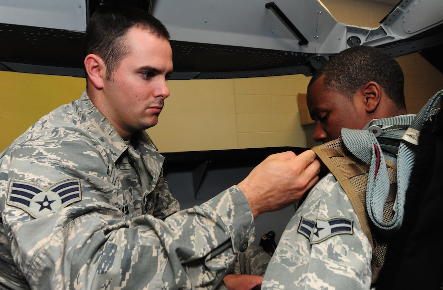 Senior Airman Ethan Mason shows fellow 509th Operations Support Squadron aircrew flight equipment technician Airman 1st Class Dalvin Washington how to attach a night vision device on an Airsave survival vest at Whiteman Air Force Base, Mo., July 16, 2013. This was done as part of a training scenario with the first wave of Airsave technicians, who were equipped to then train other OSS members. (U.S. Air Force photo by Staff Sgt. Nick Wilson/Released)
