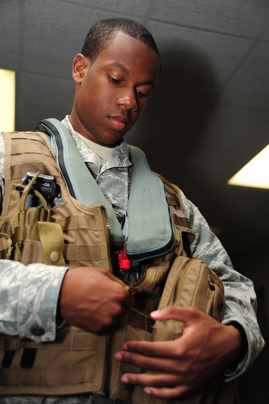 Airman 1st Class Dalvin Washington, 509th Operations Support Squadron aircrew flight equipment apprentice, dons Airsave vest during a training scenario at Whiteman Air Force Base, Mo., July 16, 2013. The vest is made of modular lightweight load-carrying equipment consisting of a basket weave-type strapping system that allows for the addition of various attachments and accessories. (U.S. Air Force photo by Staff Sgt. Nick Wilson/Released)