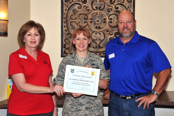 GOODFELLOW AIR FORCE BASE, Texas-- Bill Nikolauk, 1st Community Federal Credit Union president, and Skelene Black, branch manger, accept the 2012 Air Force Distinguished Bank and Credit Union of the Year Award from Col. Kimberlee Joos, 17th Training Wing Commander, July 26. 1st Community Federal Credit Union was selected out of 37 entries to be recognized for its outstanding support provided to Team Goodfellow and the overall Air Force mission.