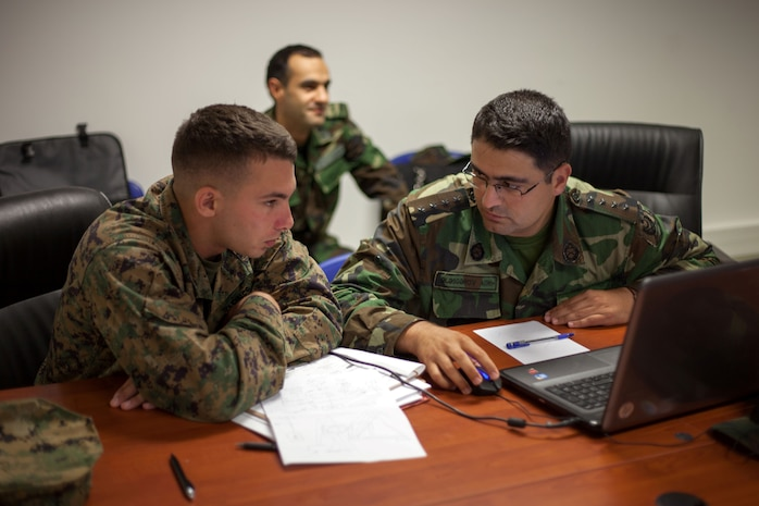 U.S. Marine Corps 1st Lt. Julian D'Orsaneo (left), communications officer for Black Sea Rotational Force 13, discusses tactical employment of communications assets with his counterpart from Azerbaijan's Operational Capabilities Concept battalion during a bilateral staff planning session in Novo Selo Training Area, Bulgaria, July 21, 2013. BSRF-13 focuses on stability, counter-insurgency, and peacekeeping operations, in order to build partner-nation capacity, enhance interoperability between countries and increase overall effectiveness of participating military forces.