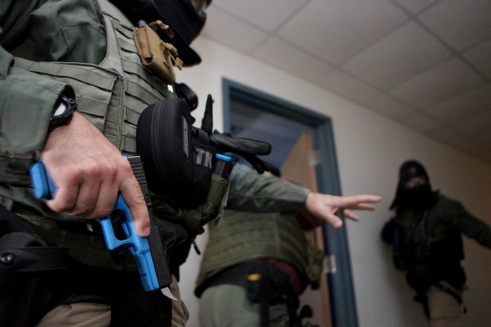 Marine Corps police officers with the Special Reaction Team perform room-clearing operations alongside the U.S. Marshals Gulf Coast Regional Fugitive Task Force during a training exercise at the Marine Corps Support Facility, July 2. This is one of multiple joint-training evolutions in which the SRT has honed their skills as a fully-functional force capable of addressing any high-risk situation that occurs at MARCORSPTFAC. (U.S. Marine Corps photo by Cpl. John M. McCall)
