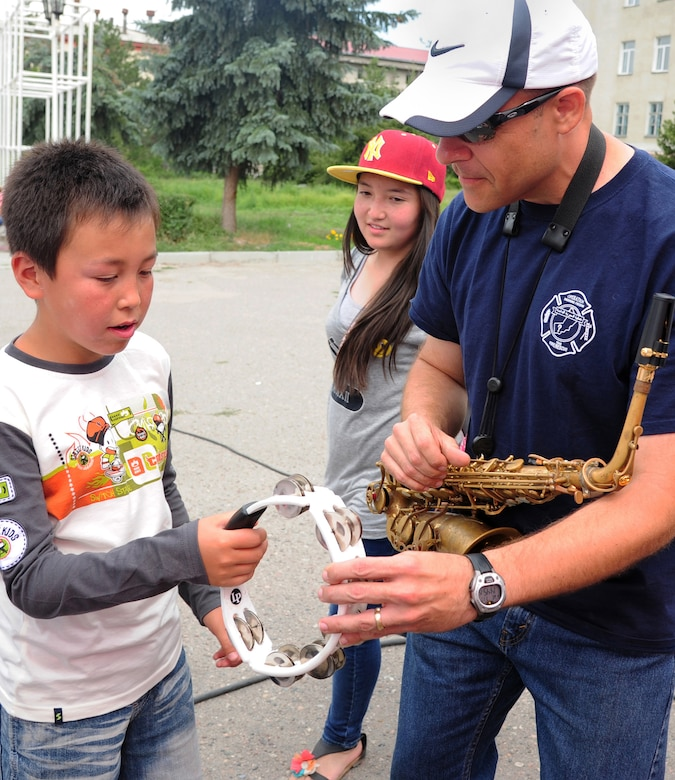 Technical Sgt. Christopher Stelling, U.S. Air Forces Central Command band, Full Spectrum saxophone player, teaches a Kyrgyz boy how to play a tambourine in Karakol City central square, Kyrgyzstan, July 17, 2013. The AFCENT band toured four local towns, bringing American music to all ages. (U.S. Air Force photo/Staff Sgt. Krystie Martinez)