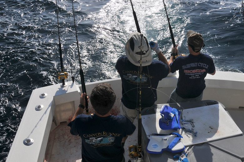 (L-R) Captain Deane Lambros and Mate and second Captain Greg Rybak, both of Canyon Runner Sportfishing, and U.S. Air Force Tech. Sgt. Keith Williams, weapons systems specialist with the 177th Fighter Wing New Jersey Air National Guard, work together to reel in a mahi mahi at the Hudson Canyon, Atlantic Ocean on July 3, 2013. (U.S. Air National Guard Photo by Master Sgt. Andrew J. Moseley/Released)