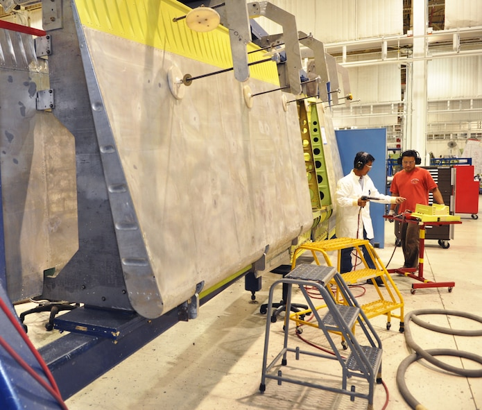 Elton Nguyen, left, and Thien Le ready the PCU fitting before placing it on the rudder. The rudder is suspended in a brace while the work is performed. Cranes, suspended from overhead beams, and dollies move the rudders from one work station to the next. Both Mr. Nguyen and Mr. Le work in the 76th Commodities Maintenance Group. (Air Force photo by Micah Garbarino)