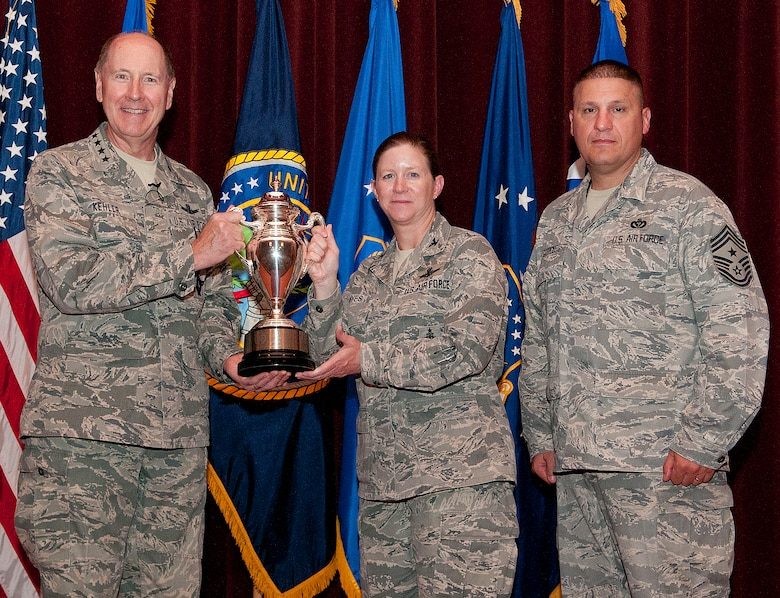 Gen. C. Robert Kehler, U.S. Strategic Command commander, presents the Omaha Trophy to Col. Tracey Hayes, 90th Missile Wing commander, and Chief Master Sgt. Mike Garrou, 90th MW command chief, during an all-call at the F.E. Warren Air Force Base, Wyo., theater July 30, 2013. The Omaha Trophy is award to the best missile wing in USSTRATCOM. (U.S. Air Force photo by R.J. Oriez)