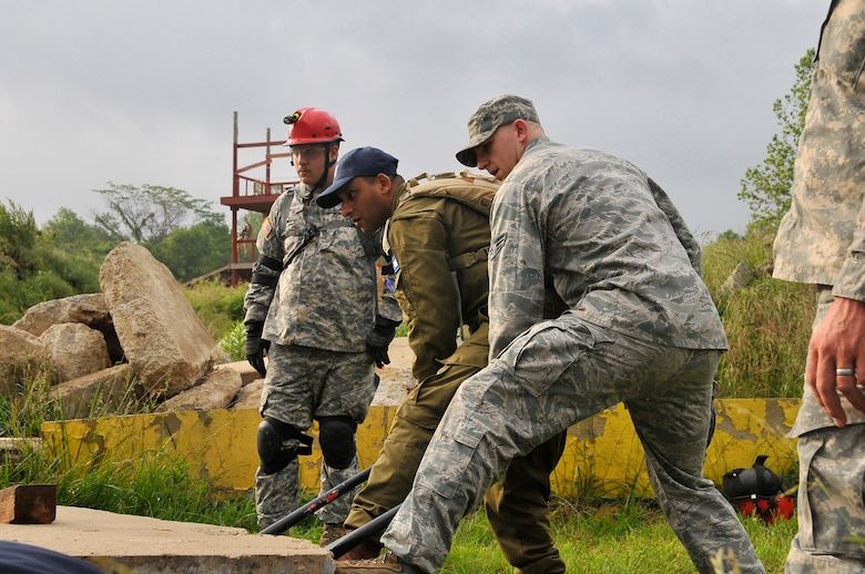 Air Force Senior Airman Cody W. Eslick, 181st Intelligence Wing, 19th CERFP, along with an Israeli soldier, use a crowbar to lift and move heavy slabs of concrete at Camp Atterbury, Edinburgh, Ind., June 10, 2013. The training conducted at Camp Atterbury involved Air and Army Guardsmen, Bloomington Fire Department and Israelis Search and Rescue team in an exercise called United Front II. (U.S. Air National Guard photo by Senior Master Sgt. John S. Chapman/Released)