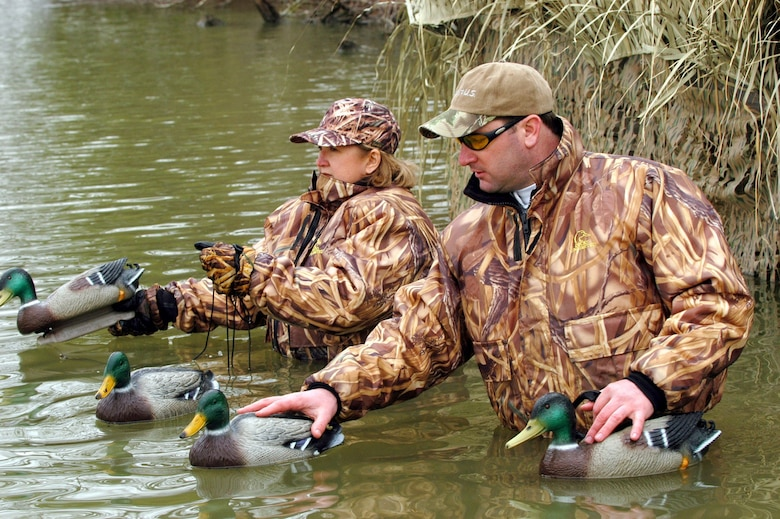 Hunters wearing hunting gear with personal flotation gear, place duck decoys.