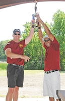 Col. William Clark, outgoing garrison commander, Fort Riley, left, and outgoing Garrison Command Sgt. Maj. Colvin Bennett Sr., right, hold the trophy for first place aloft at the conclusion of a garrison Organization Day July 12 at Moon Lake.  Photo by: Dena O'Dell, POST.