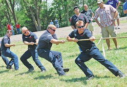 A team from the FRFD struggles in vain as they pull on the rope in a round of tug of war during a garrison organization day July 12 at Moon Lake. Throughout the afternoon, teams faced off in a variety of sporting events like tug of war, an egg toss and three-legged race.  Photo by: Julie Fiedler, POST.