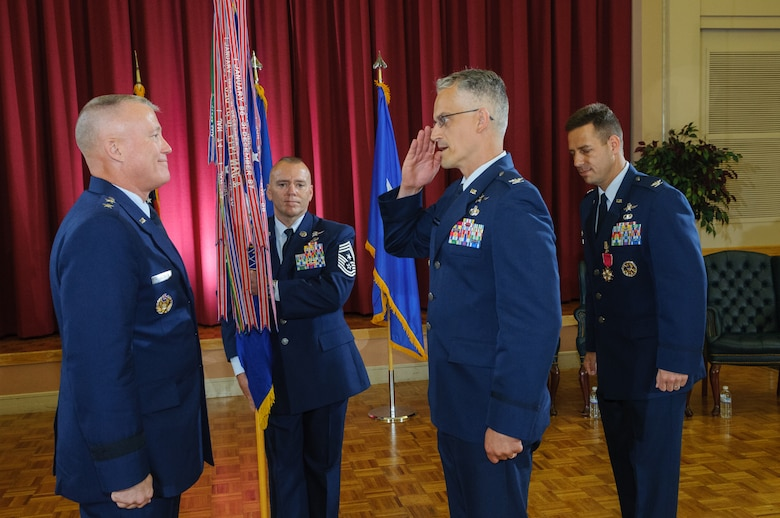 Maj. Gen. Kevin McLaughlin, 24th Air Force commander, officiates the 688th Information Operations Wing change-of-command ceremony July 23, as Col. Michael C. Harasimowicz reports having assumed command. The ceremony was held at the Joint Base San Antonio - Lackland, Texas, Gateway Club. Chief Master Sgt. William Jones, 688th IOW command chief, acts as the guidon bearer for the ceremony, a symbol of the authority being vested in the incoming commander. Col. Paul A. Welch, the outgoing commander, moves to the position of 24th Air Force vice commander. (U.S. Air Force Photo/William Belcher)