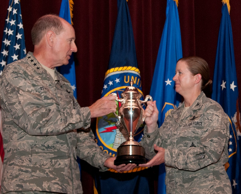 Gen. Robert Kehler, U.S. Strategic Command commander, presents the Omaha Trophy to Col. Tracey Hayes, 90th Missile Wing commander, during an all-call at the F.E. Warren Air Force Base, Wyo., theater July 30, 2013. The Omaha Trophy is awarded to the best missile wing in USSTRATCOM. (U.S. Air Force photo by R.J. Oriez)