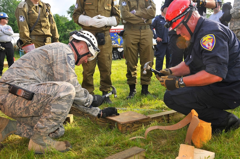 Air Force Master Sgt. Sean S. Fretwell, 181st Intelligence Wing, 19th CERFP, together with a Bloomington fire fighter, constructs a wall brace to support an entrance to a building at Camp Atterbury, Edinburgh, Ind., June 10, 2013. The training conducted at Camp Atterbury involved Air and Army Guardsmen, Bloomington Fire Department and Israelis Search and Rescue team in an exercise called United Front II. (U.S. Air National Guard photo by Senior Master Sgt. John S. Chapman/Released)