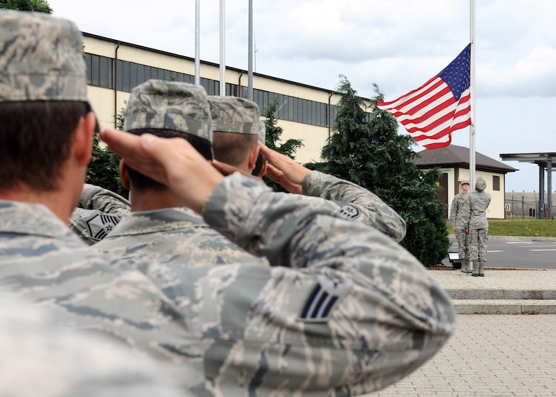 SPANGDAHLEM AIR BASE, Germany – Base members salute as honor guard members lower the U.S. flag at a new retreat ceremony July 29, 2013. U.S. Air Force Chief Master Sgt. Matthew Grengs, 52nd Fighter Wing command chief master sergeant, initiated the base-wide retreat ceremony as a way for Spangdahlem Airmen to demonstrate military customs and courtesies. (U.S. Air Force photo by Staff Sgt. Daryl Knee/Released)