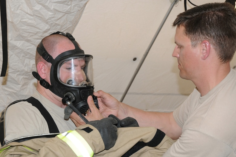 """Maj. Tim Pegg (right), FSRT OIC, helps Tech. Sgt. Branden Hassett (left), FSRT Team Leader, feed his mask through the hood of his Lion MT94 Chemical Suit at Camp Ashland, Nebraska on May 15, 2013. Teamwork is necessary to ensure that all of the suits are properly sealed and safe for the wearer to enter the """"hot zone"""". (U.S. Air National Guard photo by Tech. Sgt. Sara M. Robinson/Released)"""