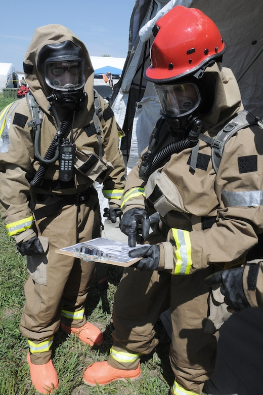 """Staff Sgt. Ryan King (left), FSRT team member, and Staff Sgt. Jonathan Clayberg (right), FSRT team member review a site map for known fatalities before they enter the """"hot zone"""" at Camp Ashland, Nebraska, on May 17, 2013. A reconnaissance team enters the area first and comes back with mark maps so the team can develop a plan for their recovery mission.  (U.S. Air National Guard photo by Tech. Sgt. Sara M. Robinson/Released)"""