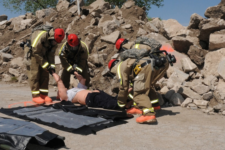 """The FSRT team loads a 200 pound mannequin onto a litter to be removed from the """"hot zone"""" at Camp Ashland, Nebraska on May 17, 2013. Mannequins are used to represent casualties to make the scenario as realistic as possible for the team.  (U.S. Air National Guard photo by Tech. Sgt. Sara M. Robinson/Released)"""