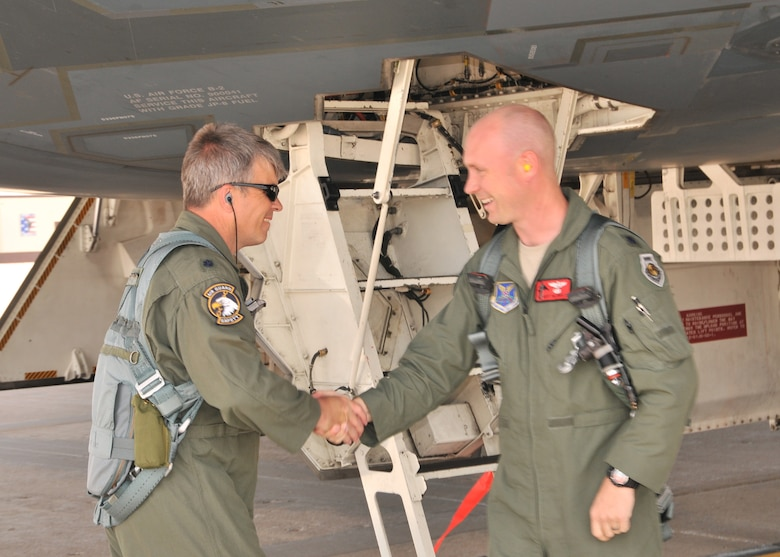 "Lt. Col. Michael Means (left) greets Lt. Col. Geoff Billingsley at the hatch to the B-2 ""Spirit of Hawaii"" during their fini flights, June 1, 2013, Whiteman AFB. Both pilots, members of the 131st Bomb Wing, Missouri Air National Guard, are moving on to new job assignments. Billingsley, who has over 1200 B-2 flying hours, is departing the aircraft and Means is continuing on for his own final flight.  Means holds the B-2 flying hours record for the Air National Guard with 1765.8 hours and is second ranking of both active and guard pilots (retired and currently flying). (U.S. National Guard Photo by Senior Master Sgt. Mary-Dale Amison/RELEASED)"