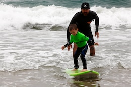 Surfer Mitch Abshere teaches 4-year-old Noah, the basics of how to stand on a surfboard during the Hurley surf event held at Del Mar Beach Resort here June 2. Hurley's summer surf tour travels around the country to give children an opportunity to learn from and ride with professional surfers. Abshere is a professional surfer who rides for the Hurley surf team and the owner of Captain Helm surf shop, the Captain Fin Co., and the wetsuit company Sea Vessel.