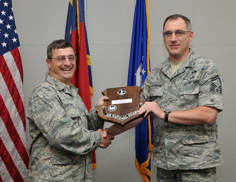 """On May 16, 2013, Air Force Col. Peter """"Puck"""" Sartori, Director of Installations and Mission Support and The Civil Engineer for the Air National Guard at Joint Base Andrews, Maryland, visited the 145th Airlift Wing, North Carolina Air National Guard base to present the Colonel Fredrick J. Riemer Award to Senior Master Sgt. Kenneth Jacobson, Emergency Management Flight Superintendent, 145th Civil Engineering Squadron. This annual award is in recognition of the best CE Readiness Flight from all Air Reserve components in the United States that best demonstrates exemplary performance in support of the engineer readiness mission. (U.S. Air National Guard photo by Tech. Sgt. Patricia Findley/Released)"""