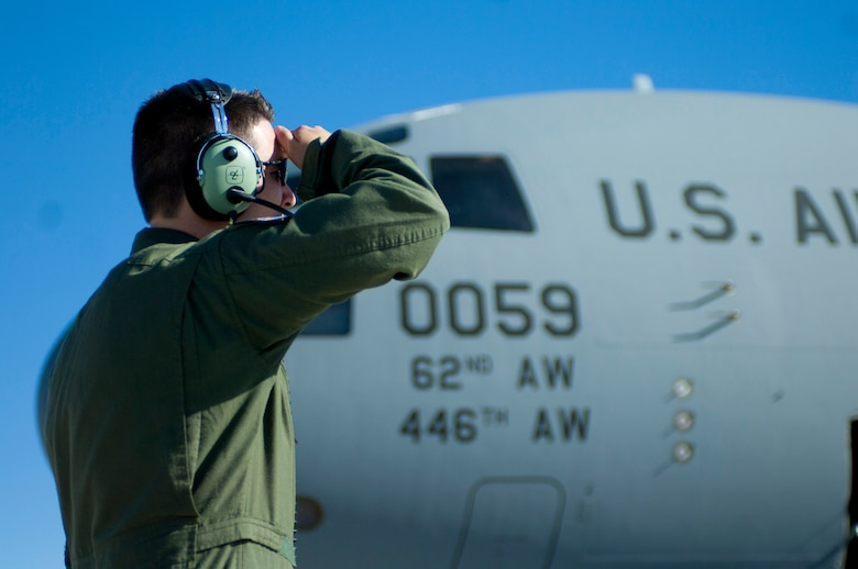 Staff Sgt. Steven Doubler, a loadmaster with the 62nd Airlift Wing, Joint Base Lewis-McChord, Wash., assists the pilot in pre-flight checks May 31, at Nellis Air Force Base Nev. A loadmaster's duties include mathematically pre-planning the correct placement of the load on the airplane, providing passenger comfort and safety, securing cargo and taking part in airdrop operations. (U.S. Air Force photo by Airman 1st Class Joshua Kleinholz)
