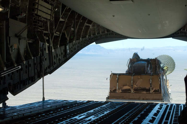 A piece of heavy land-moving equipment is dropped out of the back of a C-17 Globemaster III May 31, over the Nevada Test and Training Range. As part of the Joint Forcible Entry exercise, heavy equipment was dropped into simulated-contested drop zones to assist forces on the ground. (U.S. Air Force photo by Airman 1st Class Joshua Kleinholz)