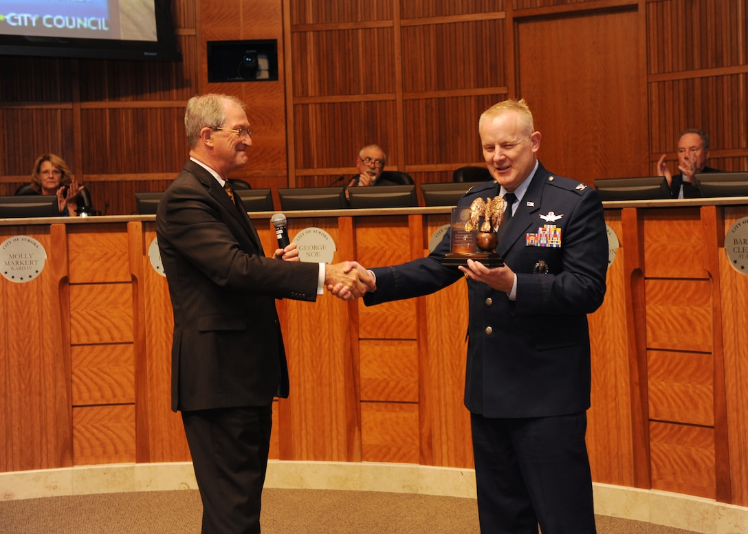 Col. Dan Dant, 460th Space Wing commander, receives an award from Aurora Mayor Steve Hogan and the Aurora City Council members, June 3, 2013, at the Aurora Municipal Center, Colo. The mayor presented Dant with an award, thanking him for his time and dedication to the community and wished him luck on his upcoming assignment. (U.S. Air Force photo by Senior Airman Marcy Glass/Release)