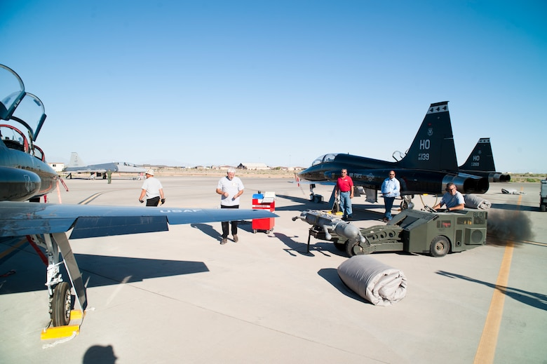 Raul Ceniceros, M1 Support Services maintainer, prepares to load a radar jammer pod onto a T-38 Talon at Holloman Air Force Base, N.M., Jun 4. For the first time, the T-38 has been modified to fit the ALQ-188 pod for use as a radar jammer. This newest addition to the T-38 will assist in its training mission by making it a more effective adversary for the F-22 Raptor during simulated combat exercises. (U.S. Air Force photo by Airman 1st Class Daniel E. Liddicoet/Released)
