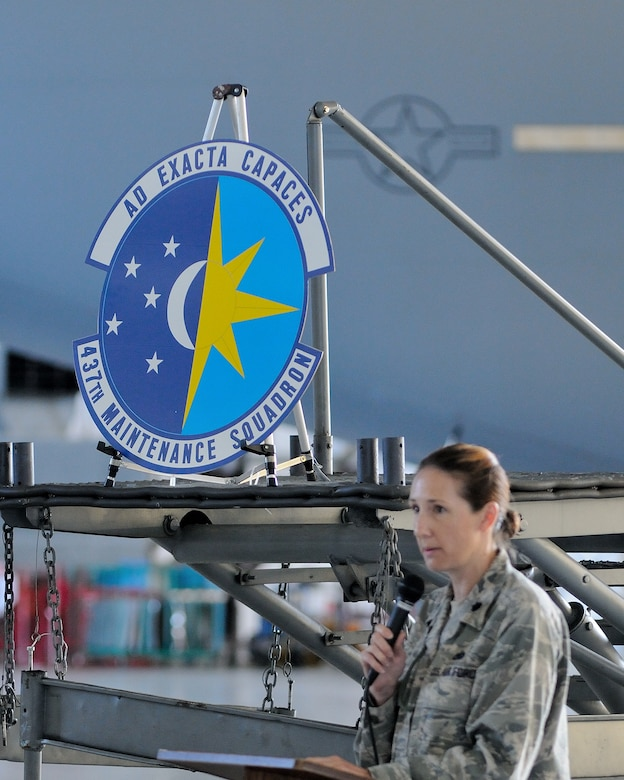 """Lt. Col Tracey Smith, 437th Maintenance Squadron commander, unveiled the squadron's new emblem during a ceremony May 30, 2013, at Joint Base Charleston – Air Base, S.C. This is the first change to the squadron's emblem since 1966. The Ultramarine Blue and Air Force Yellow represent the U.S. Air Force colors. Blue alludes to the sky, the primary theater of Air Force operations and the yellow refers to the sun and the excellence required of Air Force personnel. The background of day and night sky indicates around-the-clock maintenance operations. The sun resembles a compass rose, symbolizing the squadron's mission of support in keeping the unit's aircraft flying worldwide. The stars are in a constellation cluster, representing the teamwork required among active duty and Air Reserve component officer and enlisted members and civilians to make the mission happen. The Latin motto, """"Ad Exacta Capaces"""" expresses the spirit of the 437th MXS personnel. (U.S. Air Force photo/Master Sgt. Perry Woods)"""