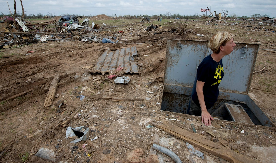 Christie England stands in the storm shelter in front of the remains of her home May 27, 2013, in Moore, Okla. England's home was destroyed in the May 20, 2013, EF-5 tornado that ripped through Moore. The storm killed 24, injured hundreds and damaged thousands of homes. (U.S. Air Force photo/Tech. Sgt. Bradley C. Church)