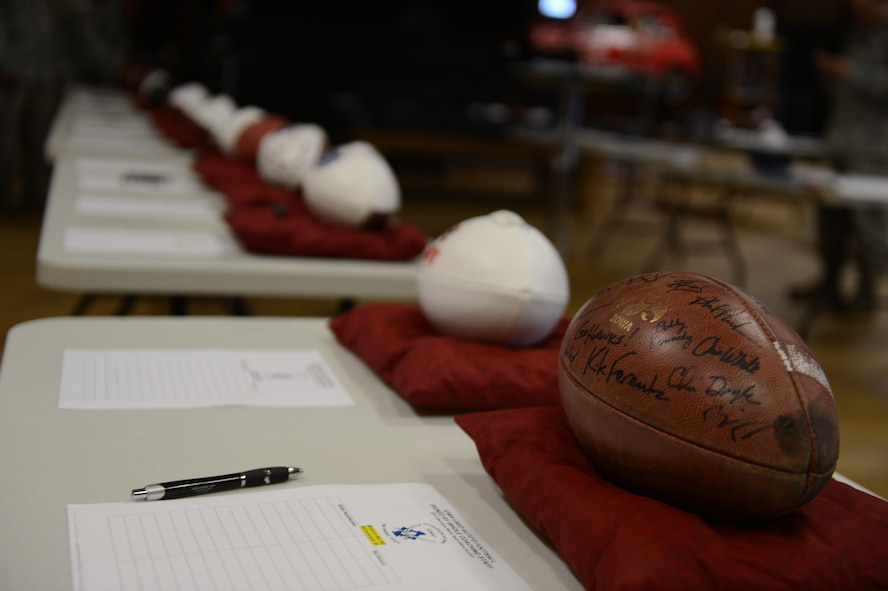 SPANGDAHLEM AIR BASE, Germany – A row of footballs signed by professional athletes rest in a line during a silent auction at the Brick House May 31, 2013. More than 500 requests for donations reached national sports stars and team coaches to support Operation Warm Heart. (U.S. Air Force photo by Airman 1st Class Gustavo Castillo/Released)