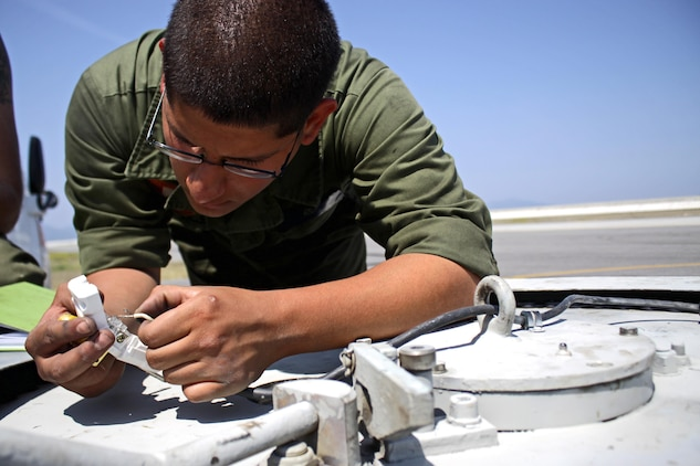 Lance Cpl. Anthony Garza, a station aircraft recovery specialist, performs maintenance work on an E-28 Emergency Runway Arresting Gear on the flightline, May 24, 2013. Recovery Marines from Iwakuni are responsible for the two most