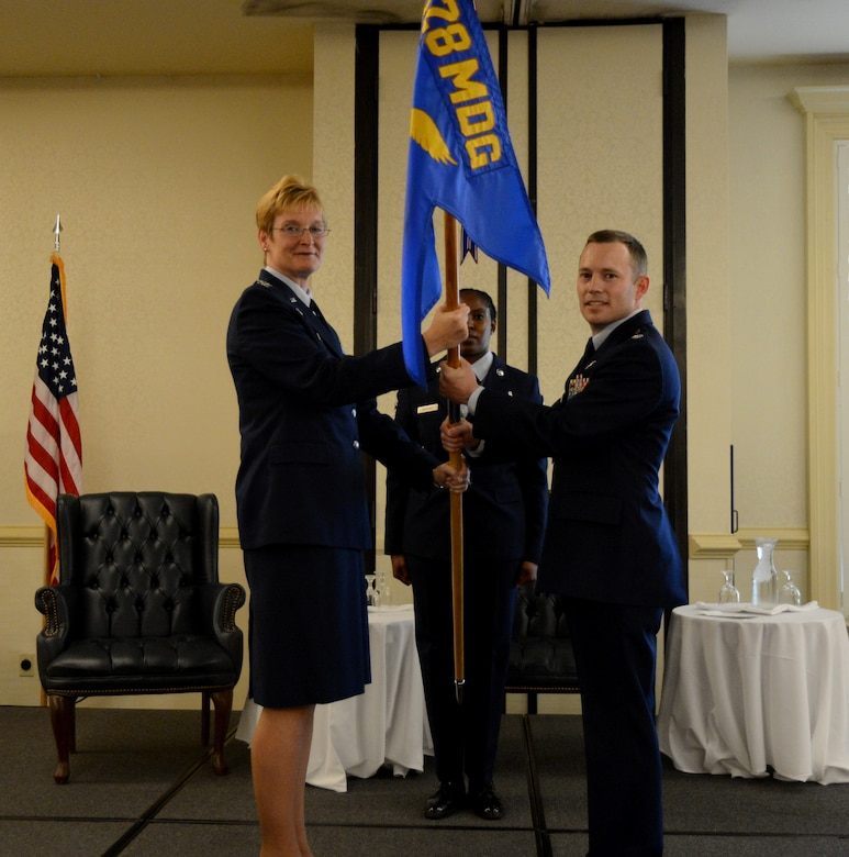 Col. Judith Hughes, 628th Medical Group commander, passes the squadron guidon to Lt. Col. Raymond Clydesdale, incoming 628th Aerospace Medicine Squadron commander, during the 628th AMDS  change of command ceremony June 3, 2013, at Joint Base Charleston – Air Base, S.C. (U.S. Air Force photo/Airman 1st Class Jasmonet Jackson)