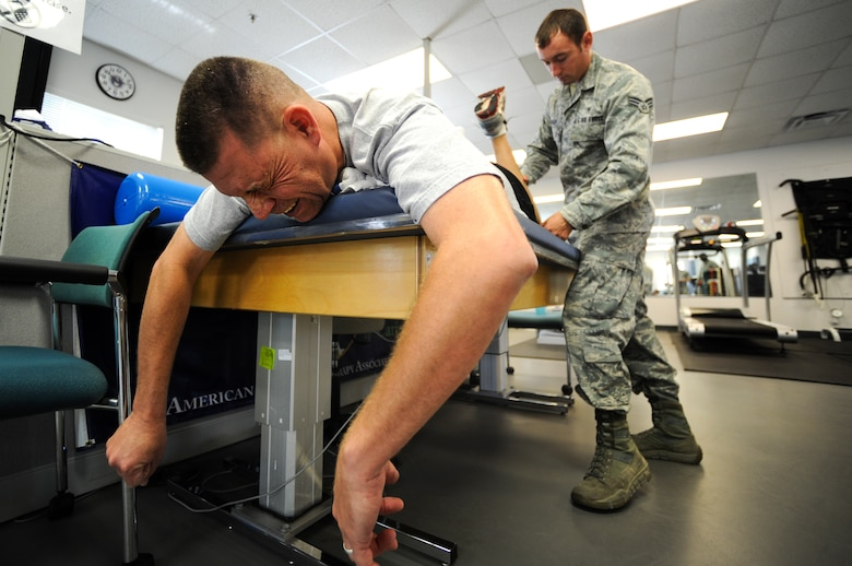 U.S. Air Force Master Sgt. David Desjardin, training management section chief for 1st Special Operations Maintenance Operations Squadron (left), gets assistance from Senior Airman David Curley, noncommissioned officer in charge of physical therapy for 1st Special Operations Medical Operations Squadron, with passive range of motion during physical training on Hurlburt Field, Fla., May 29, 2013. Physical training technicians are primarily concerned with the remediation of injuries and disabilities to promote mobility, functional ability, movement potential and quality of life. (U.S. Air Force photo/Airman 1st Class Christopher Callaway)