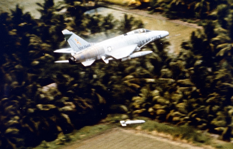 The pilot of this F-100 pulls up sharply after releasing a napalm bomb on Viet Cong concealed in the tree line in the Mekong Delta. (U.S. Air Force photo)
