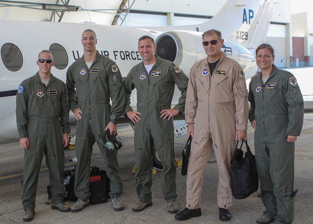 Second Lts. Chad James and Jeremy Mooney, Lt. Col. Timothy Moser, Mr. Kevin Salonman, and Maj. Carrie Register, all of the 451st Flying Training Squadron, pose for a photo in front of a modified T-1 Jayhawk aircraft before its first flight June 4, 2013 at Naval Air Station Pensacola, Fla. The aircraft has been modified for electronic warfare training, marking the first time in Air Force history that an undergraduate aviation program has formally incorporated the fundamentals of electronic warfare in flight into their syllabus. (U.S. Air Force photo by Master Sgt. Michelle Alexander)