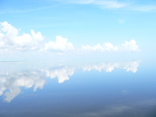 On summer afternoons, there is often a ring of clouds around Lake Okeechobee, and sometimes, it looks like the water meets the sky as the horizon on the big lake seems to disappear.