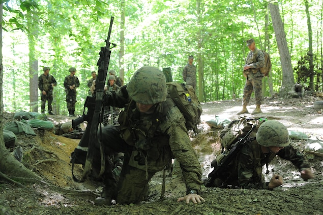 Naval Academy midshipmen drag themselves through the mud under barbed wire on the endurance course May 31, at the start of Leatherneck. The training replaces Officer Candidates School, introducing the midshipmen to Marine Corps requirements and whittling down their numbers.