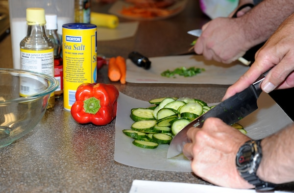 "Lt. Col. (ret.) Jim ""Stormy"" Weathers, a former B-52 navigator cuts a cucumber during the healthy cooking class.(U.S. Air Force photo by 2nd. Lt. Rachelle Smith/Released)"