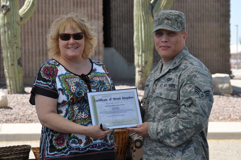 Jean Hickman, Adopt-a-Park coordinator for Tucson Clean & Beautiful, presents Senior Airman Benjamin Honken, 612th Air and Space Operations Center, with a certificate of recognition during a ceremony recognizing his units' contributions to Tucson's Adopt-a-Street program, June 6. (USAF photo by Master Sgt. Kelly Ogden/Released)