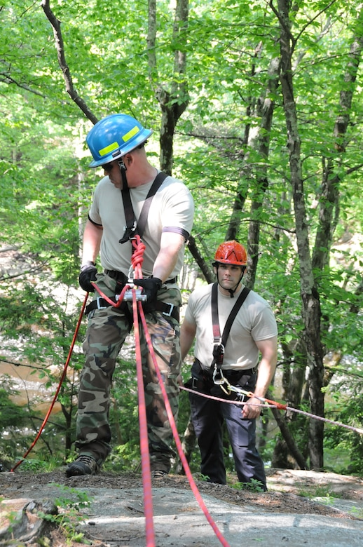 ROCHESTER, N.H. -- Tech. Sgt. Richard Wallingford rappels down a cliff here while training on high angle and low angle evacuation, June 2, 2013 as Tech. Sgt. Darrell T. Jeffers looks on. Wallingford is assigned to the 157th Civil Engineering Squadron, as a member of the Pease Urban Search and Rescue Team. (U.S. Air National Guard photo by Staff Sgt. Curtis J. Lenz/RELEASED)