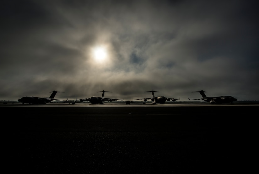 Fog rolls across the Joint Base Charleston flightline as the sun rises above four C-17 Globemaster III's June 4, 2013, at JB Charleston – Air Base, S.C. The first C-17 to enter the Air Force's inventory arrived at Charleston Air Force Base in June 1993. The C-17 is capable of rapid strategic delivery of troops and all types of cargo to main operating bases or directly to forward bases in the deployment area. (U.S. Air Force photo/Senior Airman Dennis Sloan)